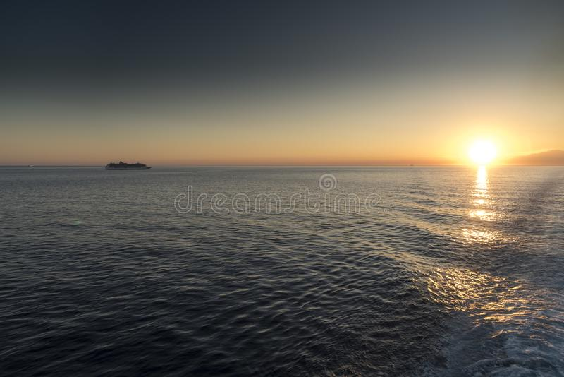 Mount Etna Sunset. The ship is The Jewel of the Seas Mount Etna is an active stratovolcano on the east coast of Sicily, Italy, in the Metropolitan City of royalty free stock images