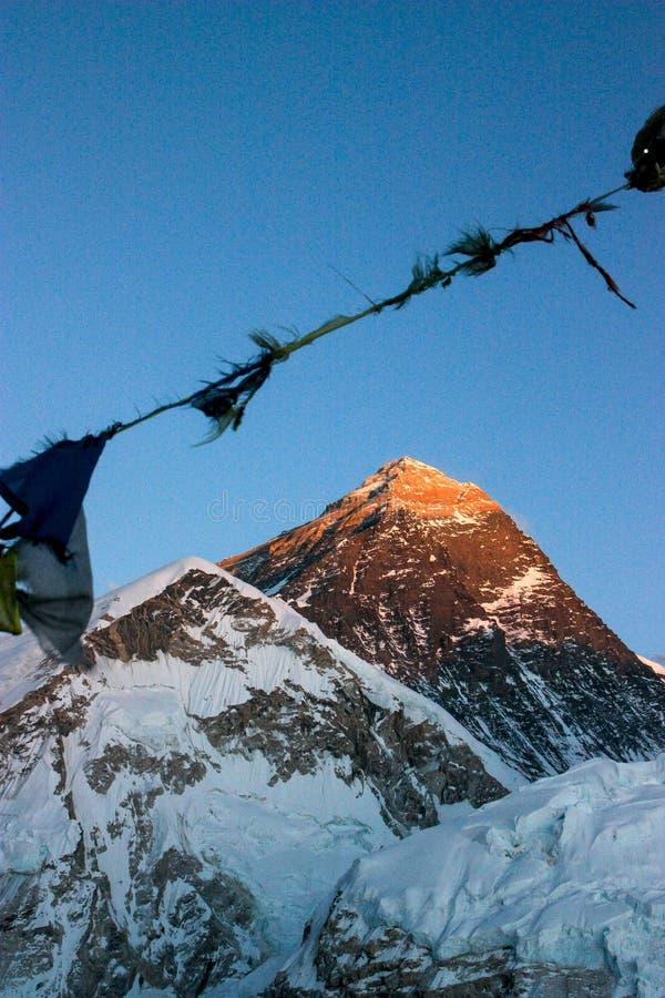Mount Everest av Himalaya, Nepal, i att blekna dagsljus med gamla bön-flaggor i forgrounden royaltyfria bilder