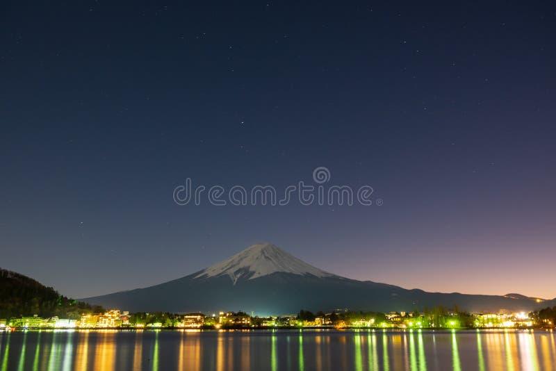 Mount Fuji вечером со светами от домов которые отражают в воду перед горой  стоковое изображение rf