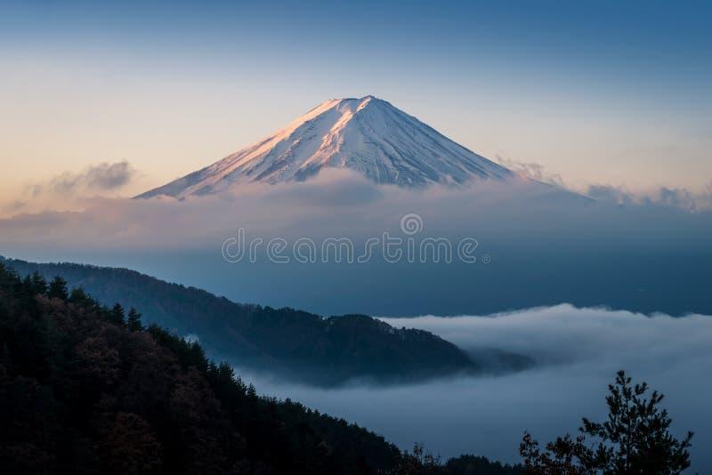 Mount Fuji enshrouded in clouds with clear sky from lake kawaguchi, Yamanashi, Japan stock photo