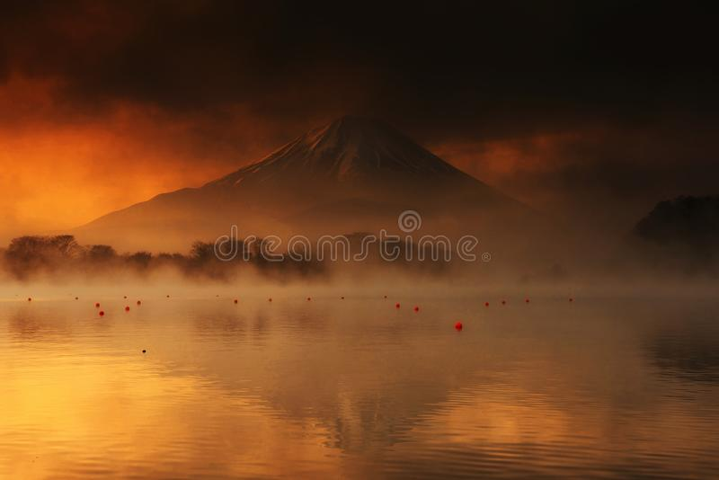 Mount Fuji and Lake Shoji at sunrise. Landscape of mountain Fujisan or Mount Fuji at sunrise with dark cloud and mist from Lake Shoji or Shojiko with reflection royalty free stock images