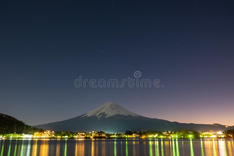 Mount Fuji at night with the lights from the houses that reflect into the water in front of the Fuji Mountain royalty free stock image