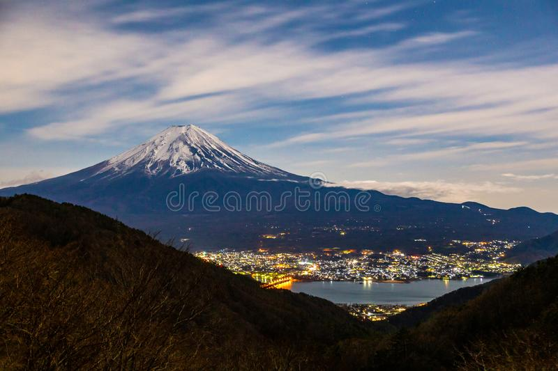 Mount Fuji, or Fuji San in Japanese, famous mountain in Japan standing tall against cloudy blue sky at night towering the stock image
