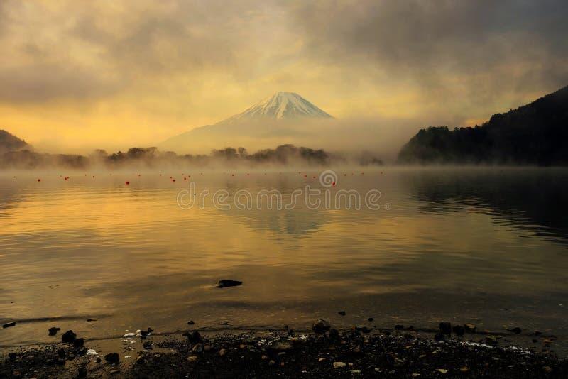 Mt. Fuji and Lake Shoji at sunrise, Japan. Mount Fujisan or Fuji with twilight sky at dawn with sunrise against dark cloud and floating mist above Lake Shoji or stock photo