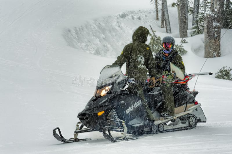Snowmobile gives snowboarder a lift stock photos