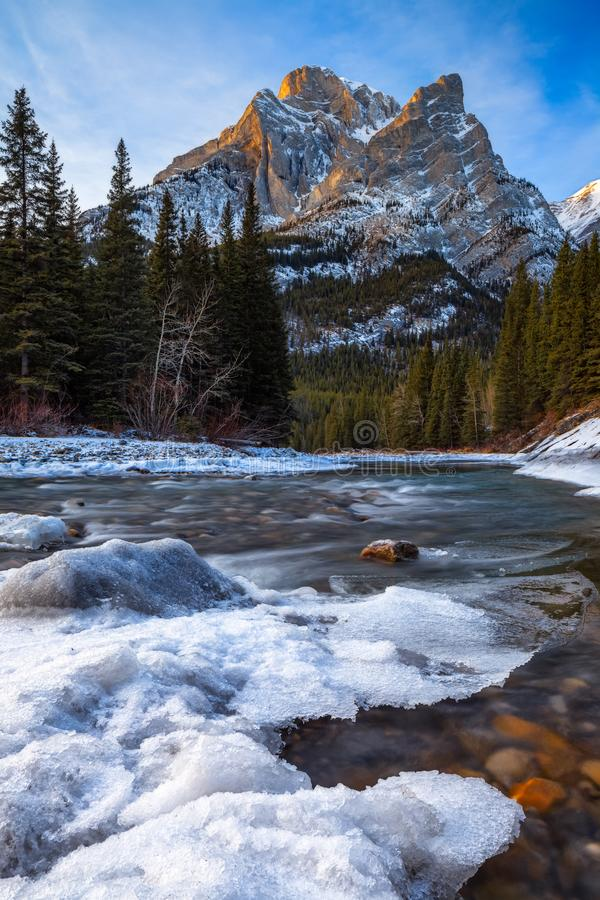 Mount Kidd, a mountain in Kananaskis in the Canadian Rocky Mountains, Alberta and the Kananaskis River in winter stock photography