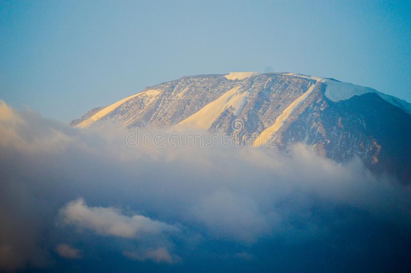 Mount Kilimanjaro beskådade från den Moshi staden arkivbilder