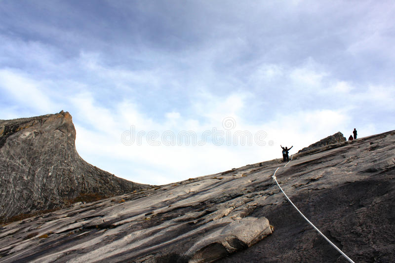 Mount Kinabalu summit with hikers in silhouette.  royalty free stock image