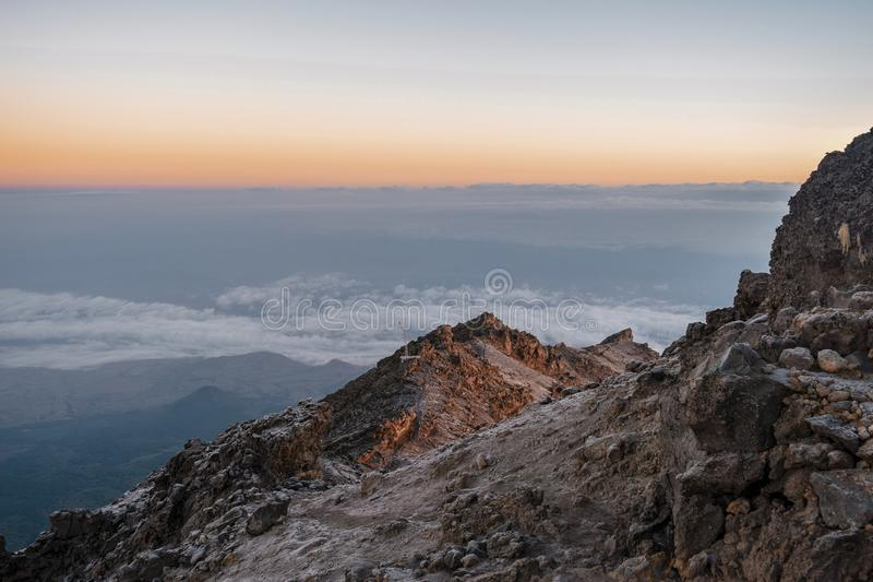 Sunrise at Mount Meru in Arusha National Park, Tanzania. Mount Meru above the clouds, Arusha National Park, Tanzania royalty free stock photos