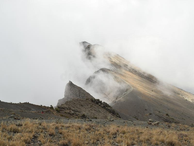 Mount Meru, Arusha National Park, Tanzania. The summit of Mount Meru partly covered by clouds, Arusha National Park, Tanzania stock images