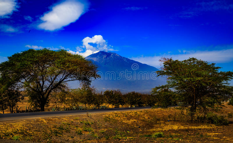 Mount Meru in Tanzania. Mount Meru is an active stratovolcano located 70 kilometres (43 mi) west of Mount Kilimanjaro in the nation of Tanzania stock images
