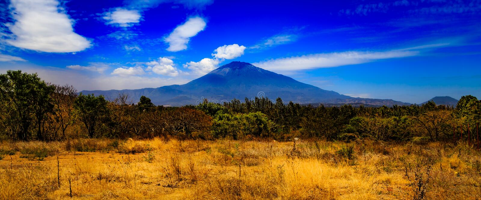 Mount Meru in Tanzania. Mount Meru is an active stratovolcano located 70 kilometres (43 mi) west of Mount Kilimanjaro in the nation of Tanzania royalty free stock photography