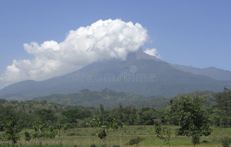 Mount Meru. In Tanzania (Africa) covered in big white clouds stock photos