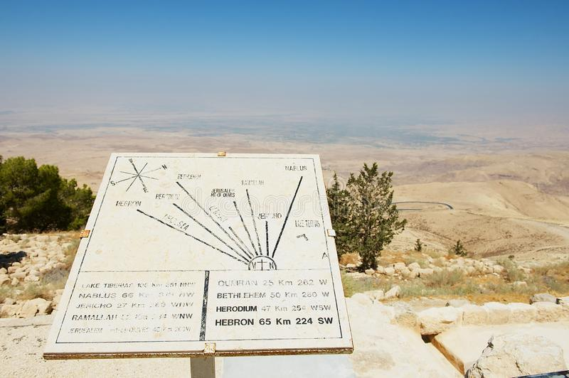 Desert mountain landscape with plaque showing the distances from Mount Nebo to various locations at Mount Nebo, Jordan. stock photos