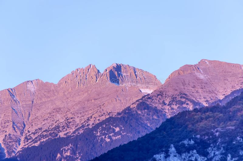 Mount Olympos with a snowy peak in the pink rays of the rising sun. Litochoro. Greece royalty free stock images