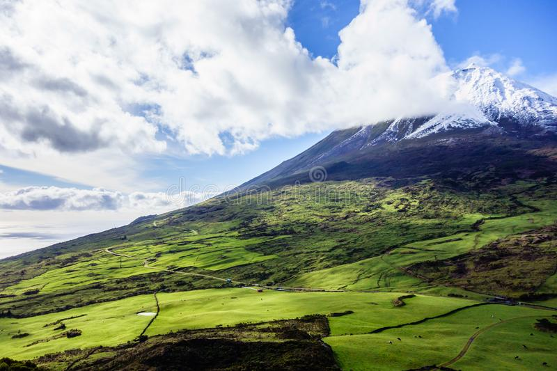 Mount Pico volcano southern slope. Mount Pico volcano summit and southern slope under blue sky and clouds, in Azores, Portugal stock images