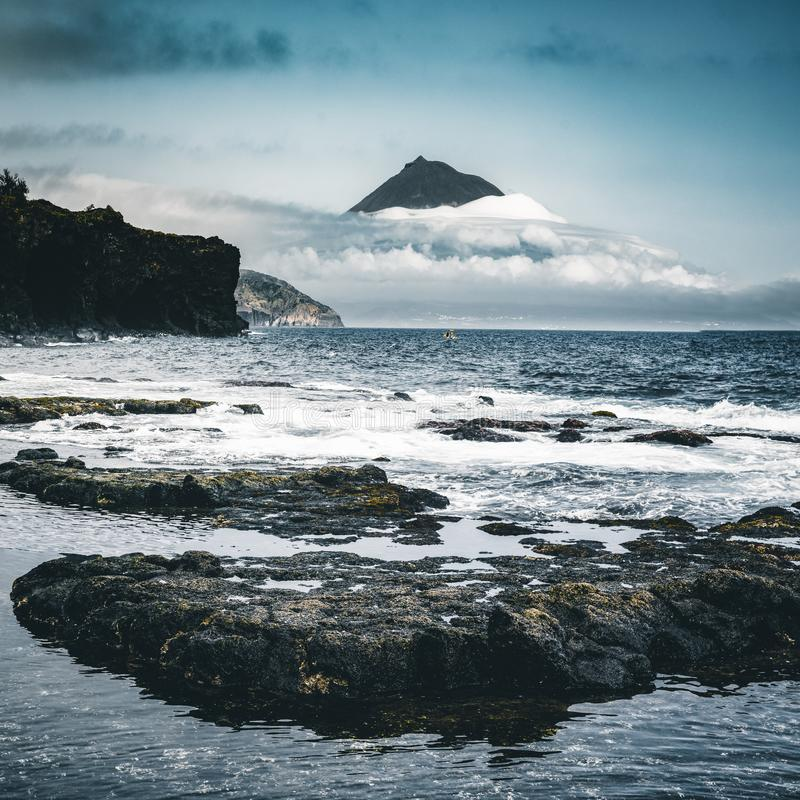 Mount Pico volcano western slope viewed from ocean with summit in clouds, seen from Faial Island in Azores, Portugal. Photo taken in Azores, Portugal stock photo