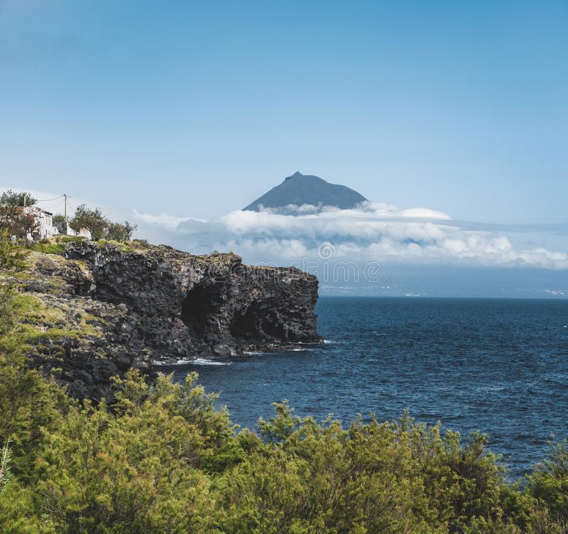 Mount Pico volcano western slope viewed from ocean with summit in clouds, seen from Faial Island in Azores, Portugal. Photo taken in Azores, Portugal stock photos