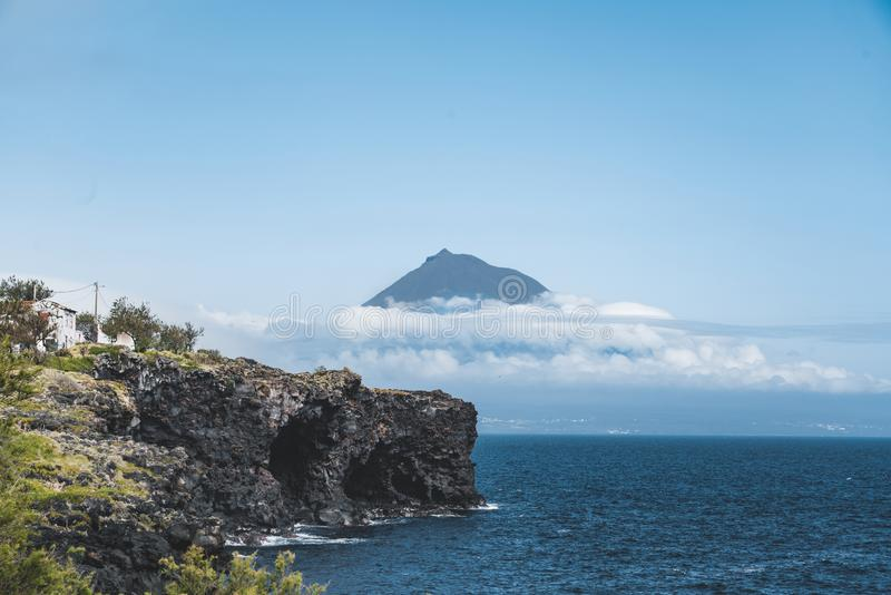Mount Pico volcano western slope viewed from ocean with summit in clouds, seen from Faial Island in Azores, Portugal. Photo taken in Azores, Portugal royalty free stock photography