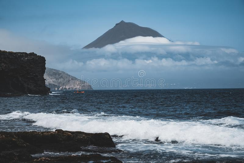 Mount Pico volcano western slope viewed from ocean with summit in clouds, seen from Faial Island in Azores, Portugal. Photo taken in Azores, Portugal royalty free stock images