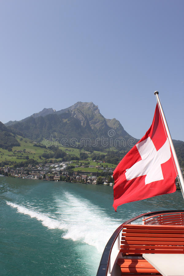 Mount Pilatus with Swiss Flag and wake of boat. stock photos