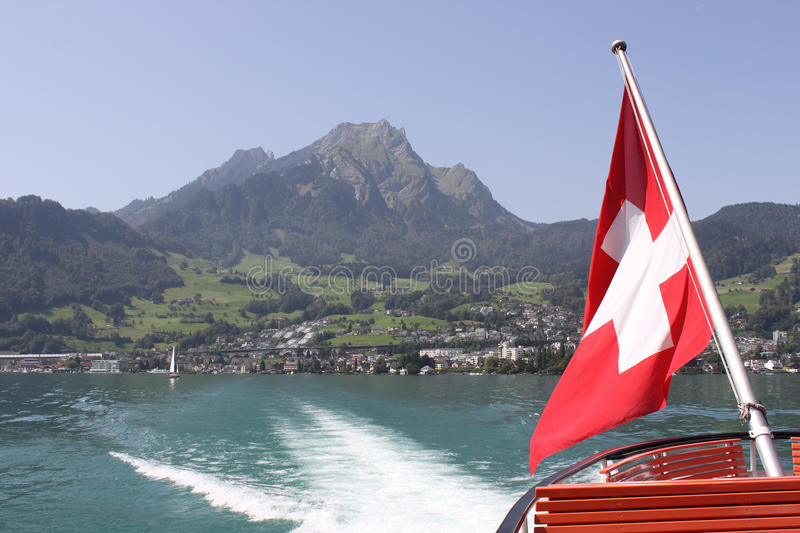 Mount Pilatus with Swiss Flag and wake of boat. Looking back from a boat on Vierwaldstatter See (Lake Lucerne) past the Swiss flag at the stern of the boat and stock photo