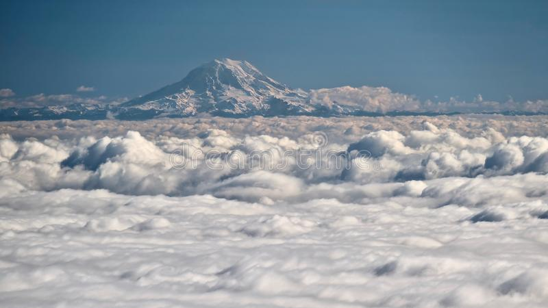 Mount Rainier covered with snow and ice above clouds. stock photos