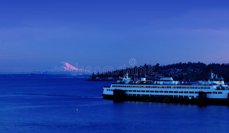 Mount Rainier, Seattle Kingston ferry boat at sunset. Mt. Rainier in pink from the sunset as the Kingston ferry loads cars. The Seattle skyline is visible across stock images