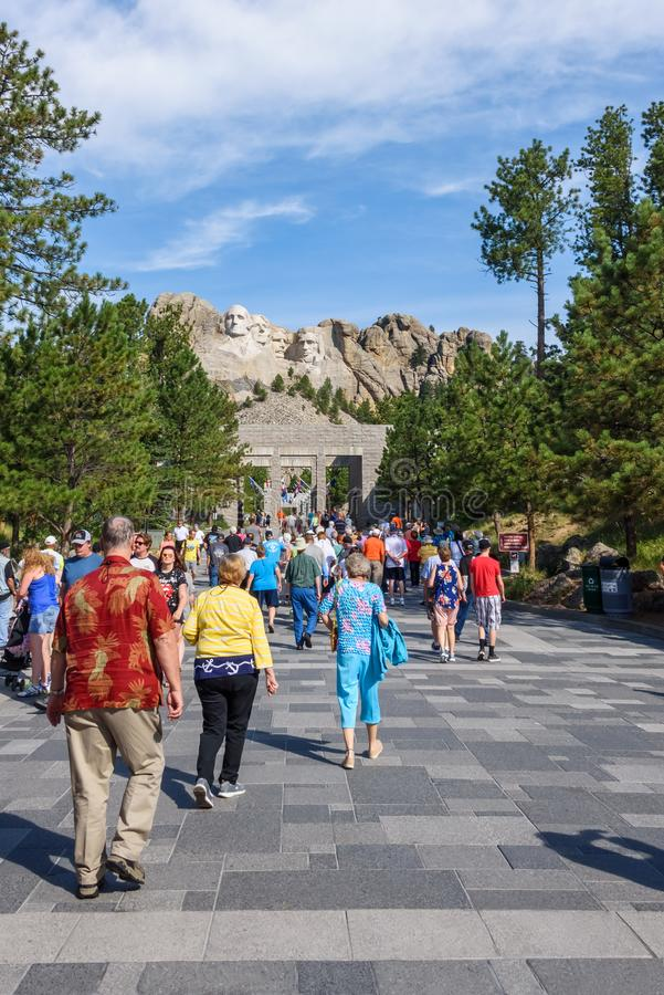 MOUNT RUSHMORE, KEYSTONE, ЮЖНАЯ ДАКОТА, США - 20-ОЕ ИЮЛЯ 2017: Посетители идут вдоль бульвара флагов с Mount Rushmore в ба стоковая фотография