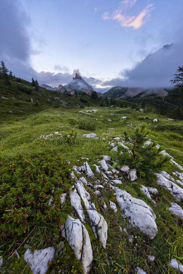 Mount Sass de Stria at sunrise, blue sky with clouds and fog, Falzarego pass, Dolomites, Veneto, Italy stock photography
