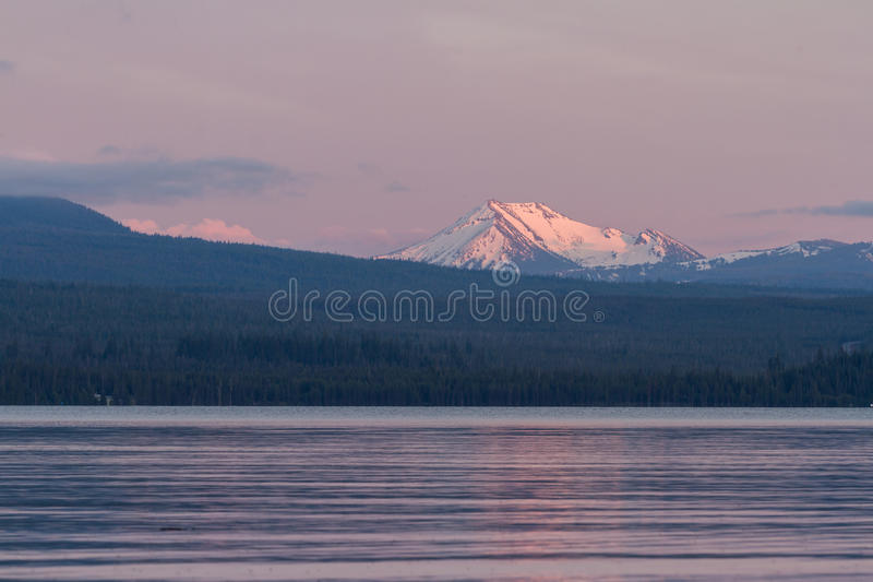 Mount Scott, Oregon,. Snow caped mount Scott from across Damond Lake at sunset stock images