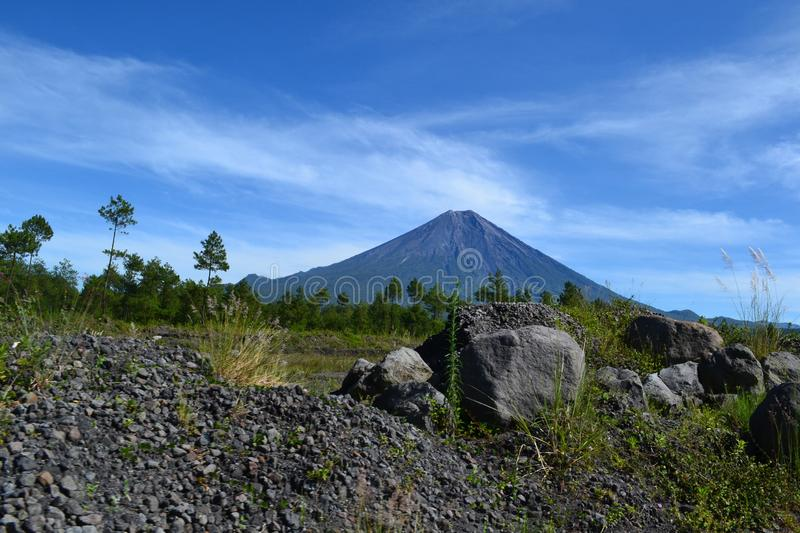 Mount Semeru in the morning. With foreground rocks adorn the morning atmosphere accompanied by cool air. The blue sky and the green foliage lead this self to be stock photography