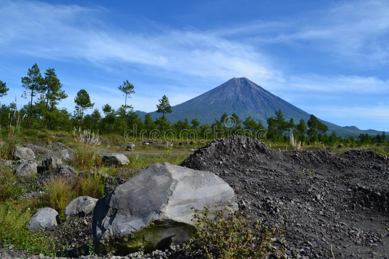 Mount Semeru in the morning. With foreground rocks adorn the morning atmosphere accompanied by cool air. The blue sky and the green foliage lead this self to be royalty free stock image