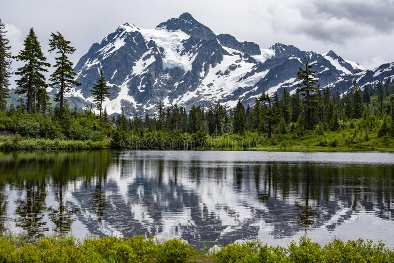 Mount Shuksan with snow and glaciers reflected in lake. Horizontal image of Mt. Shuksan in the Mt. Baker area of Washington State. The mountain is snow covered stock image
