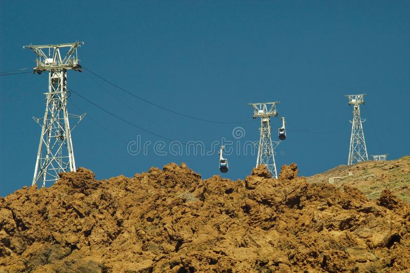 Mount Teide Cable Car. Gondolas moving up and down to top of volcano at 3,555 m altitude over the blue sky. View from bottom stock images