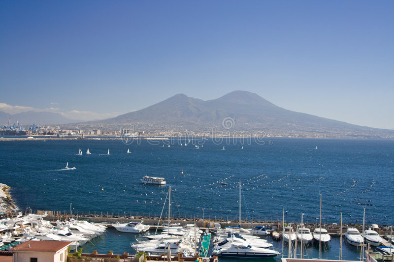 Mount Vesuvius, Naples. View of Mount Vesuvius from Naples. View of th e touristic marina and the gulf of Naples with boats sailing royalty free stock image