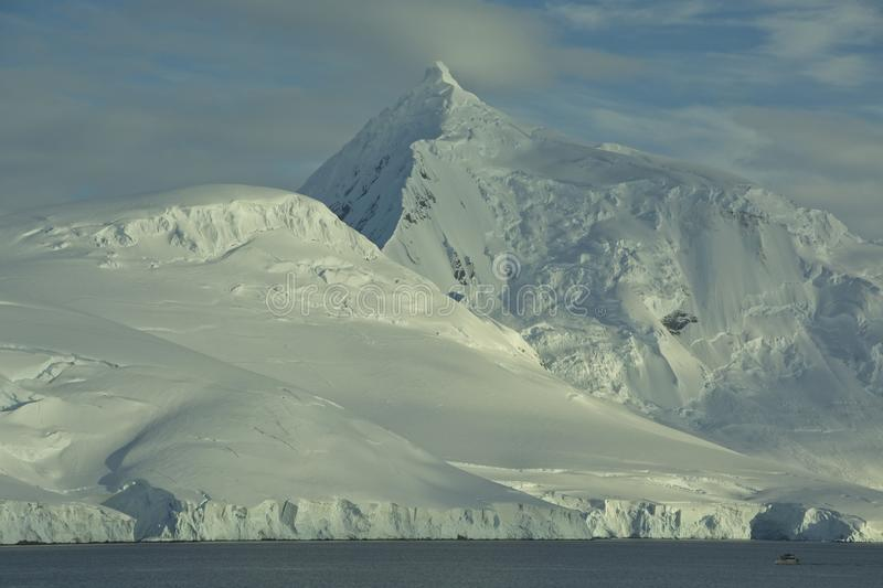 Mount William as seen from Port Lockroy, Antarctica. Majestic and pristine Mount William towers over the bay by Port Lockroy, the British historic site stock photo