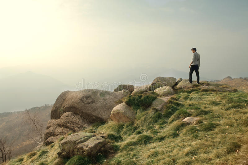 Mountain. Young man standing on the top pf a mountain stock image
