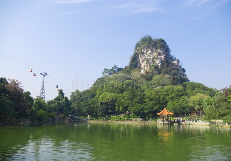 Mountain. Green edge of the lake has a stone mountain, this is the famous Chinese scenic spots in Liuzhou,Guangxi Yufeng Peak Park stock images