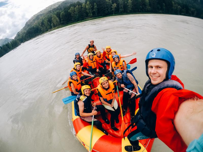 Mountain Altai, RUSSIA. July 16, 2017: man in a helmet holds an action camera and makes selfie on the background of friends with oars, rafting royalty free stock image