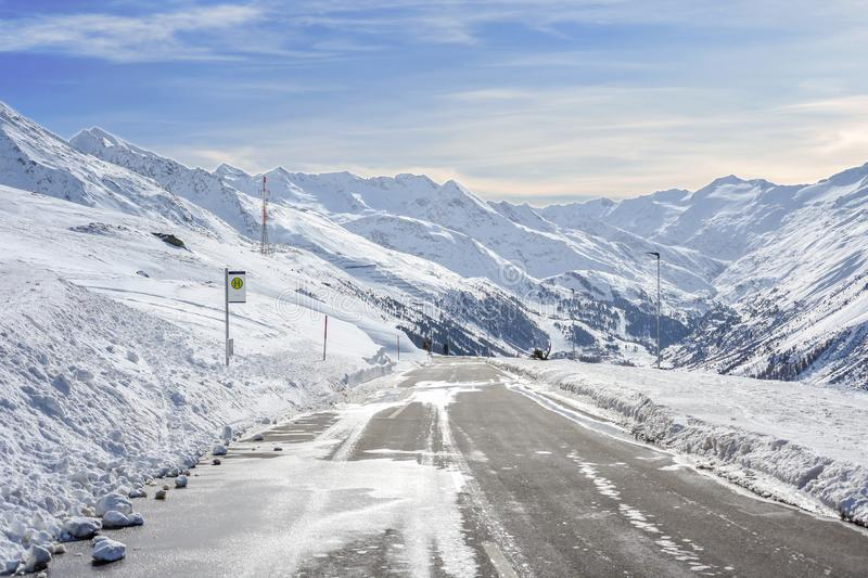 Mountain asphalt road with a lot of snow on the side and mountain sk royalty free stock image