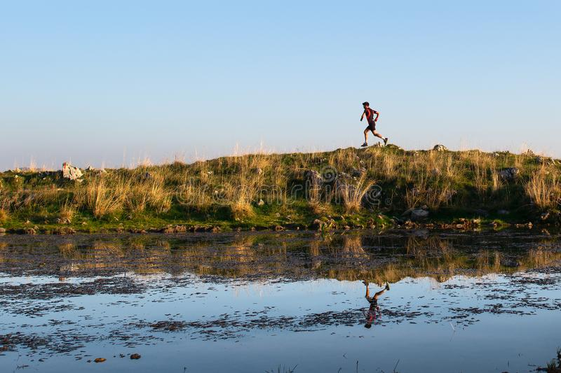 Mountain athlete is reflected in a small lake while running stock photos