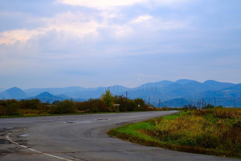 Mountain autumn landscape with road and distant mountains royalty free stock photo