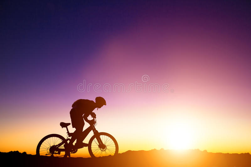 Mountain bicycle rider on the hill with sunrise. Background stock photo