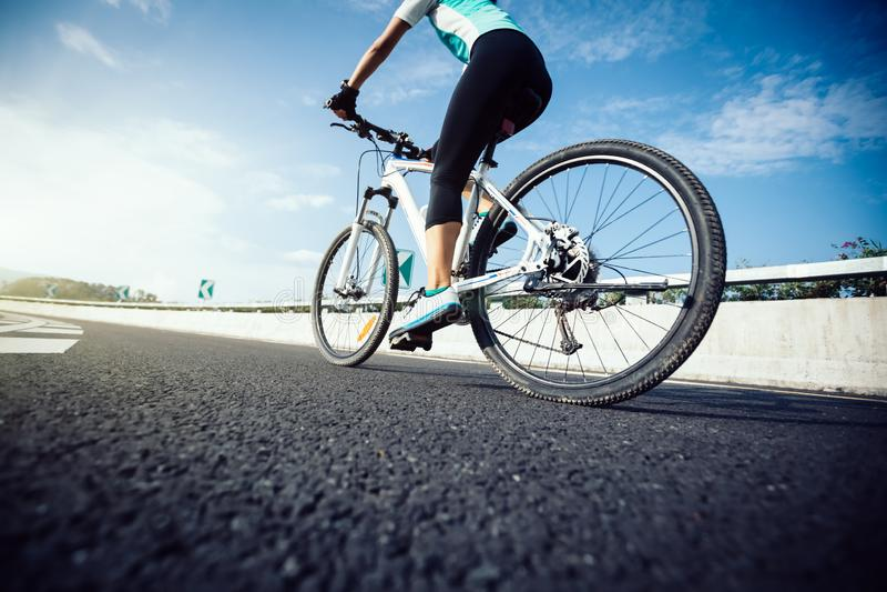 Mountain bike da equitação do ciclista na estrada fotos de stock