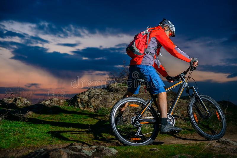 Mountain bike da equitação do ciclista na mola Rocky Trail no por do sol bonito Esportes e conceito extremos da aventura fotos de stock royalty free
