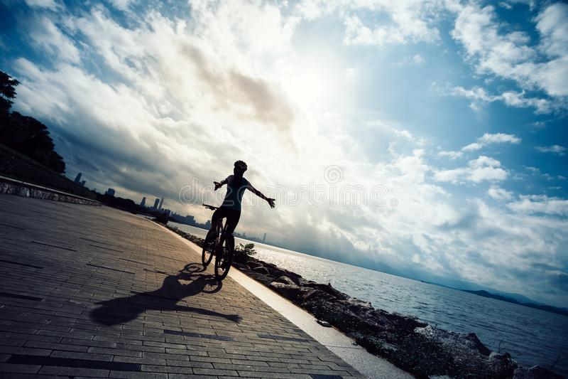 Mountain bike de ciclagem da equitação da mulher no beira-mar do nascer do sol imagens de stock