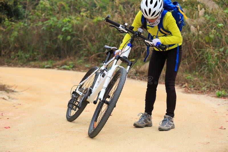 Mountain bike di guida della donna sulla traccia della foresta immagini stock