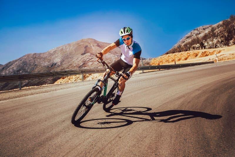 Mountain bike do passeio do homem na estrada imagens de stock
