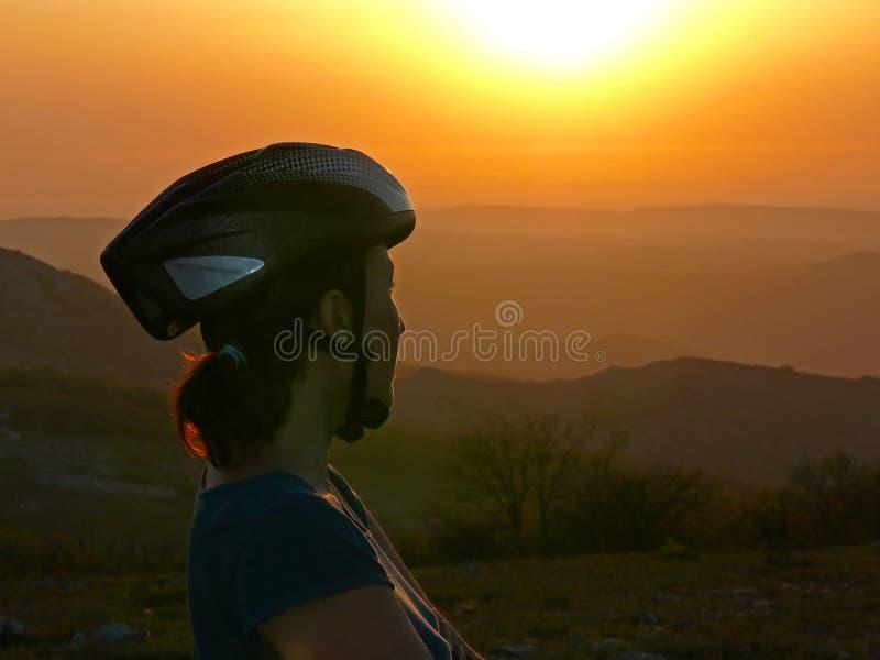 Mountain bike - donna con un casco della bicicletta che ammira il tramonto immagini stock libere da diritti